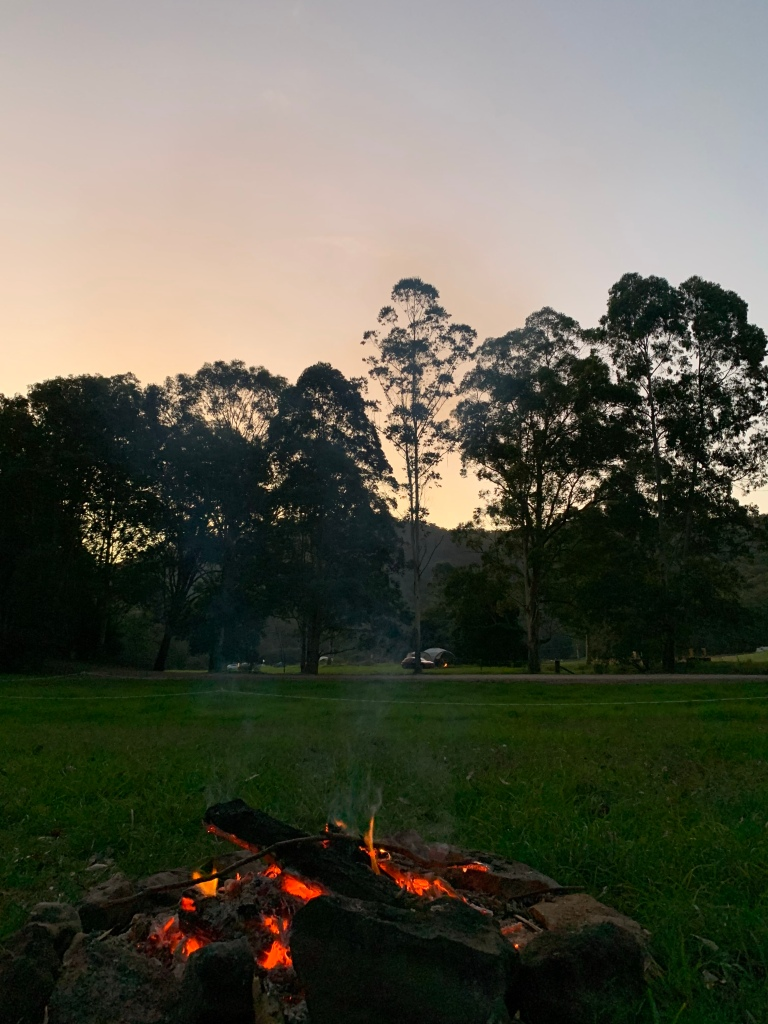 Warming up at the campfire  watching the sunset